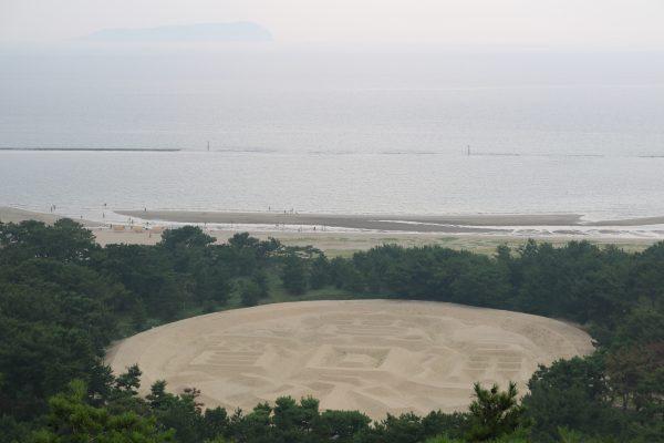 Die Zenigata-Sandskulptur. Am Horizont: Die Insel Ibukijima